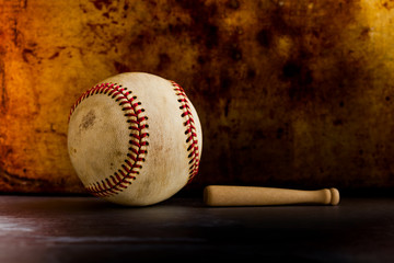 Vintage baseball and small wooden bat. Sport equipment on retro style metal texture background. copy space