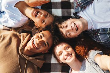 Portrait of multiethnic young friends guys and girls laughing, and lying on blanket in circle outdoor