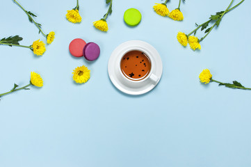 Cup of tea, colorful sweet cakes macaroons and yellow chrysanthemum on blue background. Delicious breakfast, Concept Good morning, still life with tea cup, postcard. Top view Flat lay Copy space