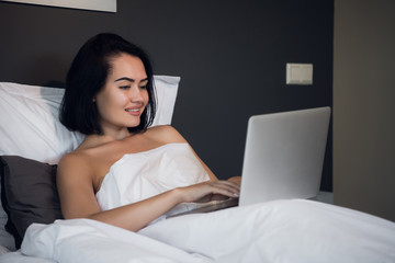 Young woman at home sitting on bed woke up browsing laptop