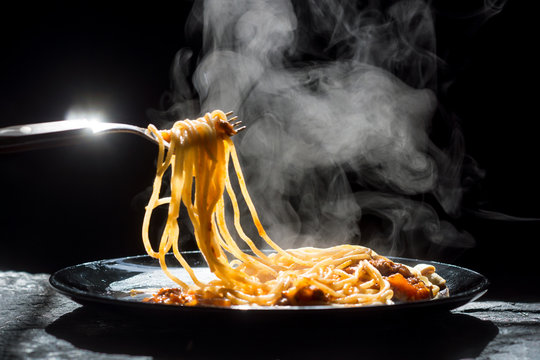 The steam from spaghetti with tomato sauce - homemade healthy italian pasta on dark background