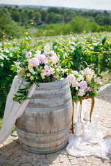 Elegant floral arrangement wedding ceremony decor with pink, white and green flowers on wooden wine barrel outdoors.
