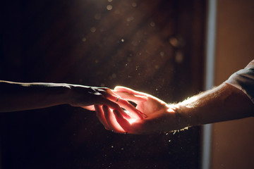 Wedding couple hands. Man and woman holding hands in the dark on the sun ray. Close up