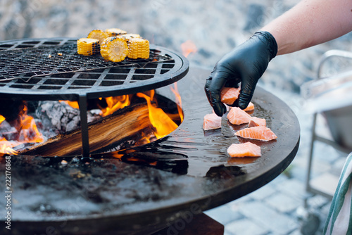 Man Cooking Corn And Salmon On The Big Round Flaming Bbq Grill Outdoors Open Fire
