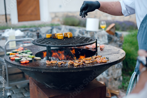 Man Salt Grilled Shrimps Corn And Vegetables On The Big Round Flaming Bbq Grill Outdoors