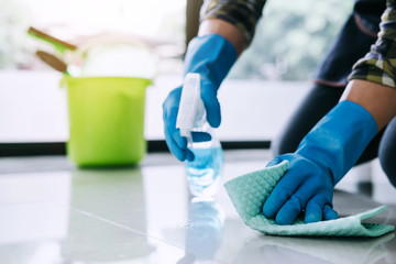Husband housekeeping and cleaning concept, Happy young man in blue rubber gloves wiping dust using...