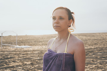 a girl wrapped in a towel stands on a sandy beach and looks into the distance