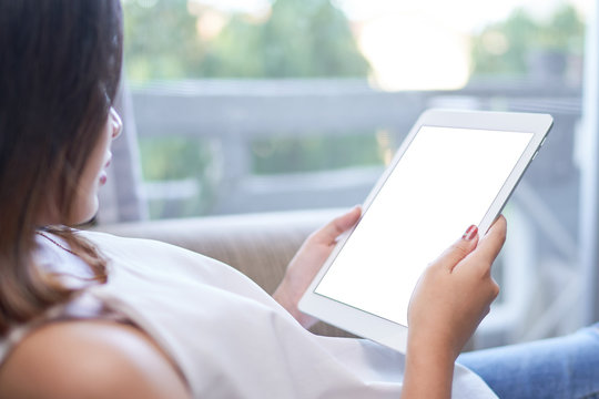 Happy cheerful asian woman sitting on the couch looking at blank screen tablet at home