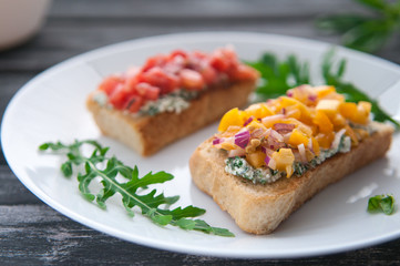Bruschetta with cheese red and yellow tomatoes on a white plate. The composition is decorated with leaves of basil, arugula, pepper and vegetables. Side view on an old wooden background. Blurred.