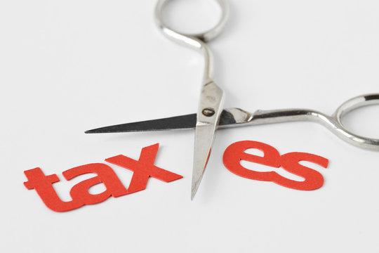 Scissors cutting the word Tax - Tax cut concept