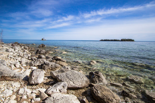 Les Cheneaux Islands In Lake Huron. Sunny day on the rocky coast of Lake Huron with the Les Cheneaux Islands at the horizon. The islanders are a popular destination for kayakers.