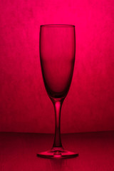 An empty transparent glass on pink background