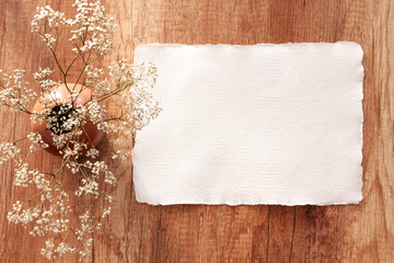 Handmade paper mockup on a wooden table with white field flowers in a vase