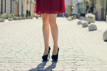 Young pretty lady walking in the city. Close up photo of long woman's legs wearing high-heels, city on the background