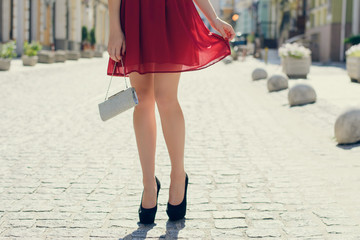 Lady having a date with her boyfriend. She is wearing  red beautiful short dress, black high-heels and holding handbag. Cropped photo of woman's legs in high-heels in the street.