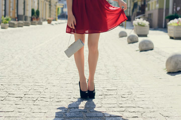 Slim lady in fashionable clothes having birthday. She is wearing elegant beautiful dress, black high heel shoes and holding a bag. Close up, cropped photo