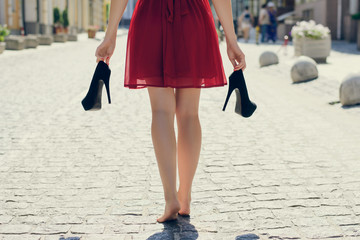 Elegant young girl in red dress with high-heels in hands, walking on the street barefoot. She is coming back home after party in the morning, view from back, close up photo of woman's long legs