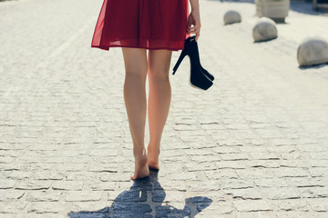 Young beautiful lady in red dress, with black high-heels in hand walking along the street barefoot; view from back, close up photo of woman's legs