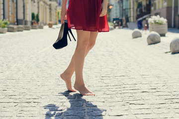 Woman in red elegant dress, holding high heel shoes in hand and walking in the city barefoot; close up photo of woman's legs without shoes