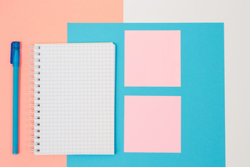 Top view photo of school supplies. Set of spiral notepad, pen and stiskers on pink and blue background. Minimal style