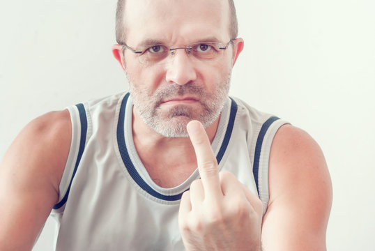 Adult angry man with a beard in a T-shirt shows a gesture of the middle finger, a threat