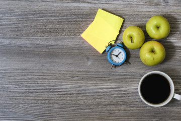 An image of apples, cup of coffee, alarm clock, stickers lying on a wooden table