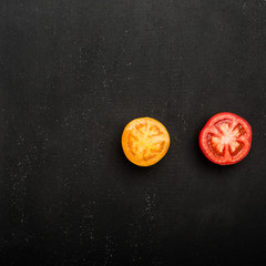 Two halves of a red, yellow tomato lie on a black background. Top view, flat lay