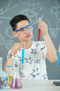 Curious pensive teen boy looking at test tubes with various reagents in his hands