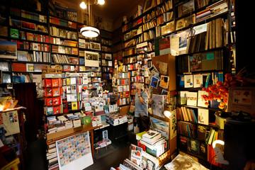 "Employee Theresa makes a phone call in Vienna's smallest bookstore ""Buchhandlung Posch"" in Vienna"