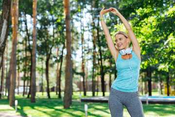 My lifestyle. Joyful young woman holding her hands up while exercising alone in the park