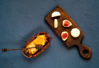 Honey in honeycombs, figs and goat cheese on wooden board on dark background of concrete. Healthy eating concept, closeup,top view, copy space