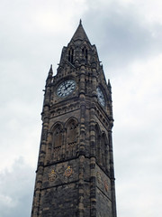 the tall gothic stone clock tower of rochdale town hall in lancashire against a blue cloudy sky