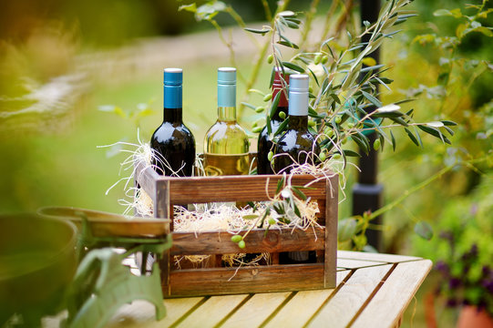 Wine bottle in a wooden crate decorated with olive branches