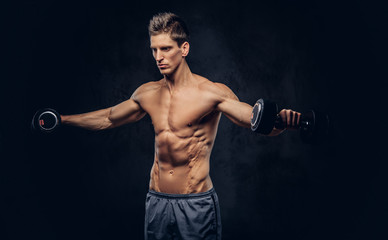 Handsome shirtless man with stylish hair and muscular ectomorph body doing the exercises with dumbbells.