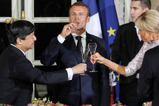 French President Emmanuel Macron drinks a glass of champagne as his wife Brigitte Macron and Japan's Crown Prince Naruhito toast at the start of an official state dinner at the Chateau de Versailles castle