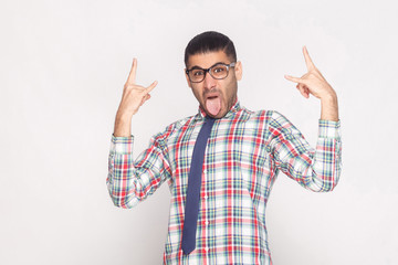 Rock and roll. crazy funny bearded businessman in colorful checkered shirt, blue tie and black eyeglasses standing, looking at camera with tongue out. studio shot, isolated on light grey background.