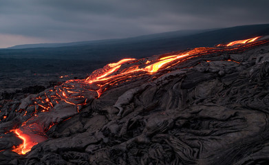 Closeup of glowing lava flow from Puu Oo in the evening on the Pali in Kalapana, Big Island, Hawaii.