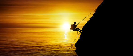 Silhouette of a beautiful athletic woman climbing a steep rock above the sea
