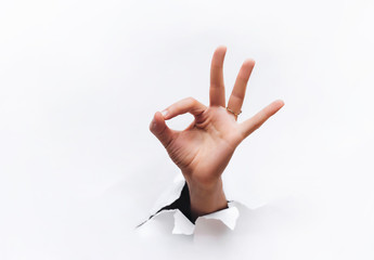 Hand ok sign. The hand came out into the hole and shows symbol of fine. Copy space.