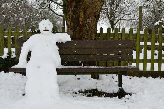 Close up of a snowman sitting on a park bench