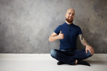 Picture of handsome positive young bald bearded guy with tattoo on his muscular arm smiling broadly at camera and making thumbs up gesture, having great day, being in good mood, showing approval
