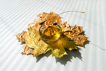 Autumn, beauty, style concept. The choice of perfume in autumn. Yellow perfume bottle and fall golden leaves on a white background. Hard light, sunlight