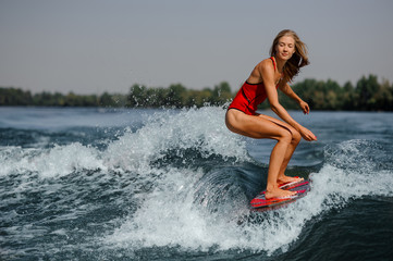 Pensive blonde girl riding on the red wakeboard