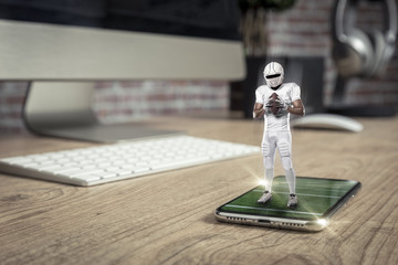 Football Player with a white uniform playing and coming out of a full screen phone on a wooden table.