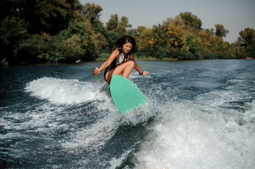 Brunette girl jumping on the wakeboard on the lake