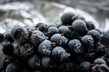 Close up of frozen black currant berries covered with hoarfrost. Selective focus