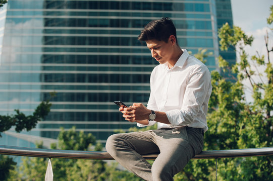 Young man browsing smartphone on railing