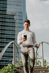Cheerful man with smartphone walking down steps