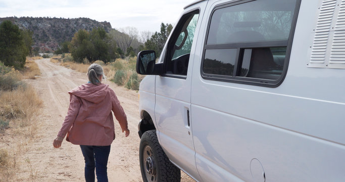 Candid senior woman in parked van stepping outside to walk away in natural park