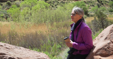 Female photographer hobbyist drinking coffee outdoors in canyon